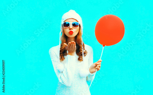 449ff4ad72e Happy young woman blowing red lips sends air kiss holding air balloon in  white knitted hat