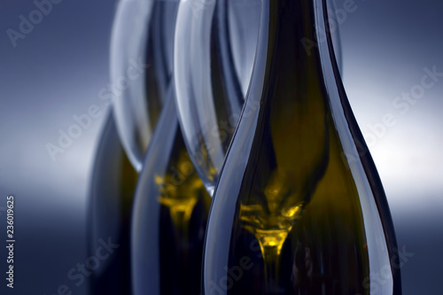 Three wine bottles and two empty wine glasses close up