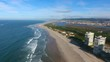 Aerial flight above sandy coastal beach with resort to right & views of mountains on horizon.
