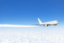 Passenger Airplane Flying At Flight Level High In The Sky Above The Clouds