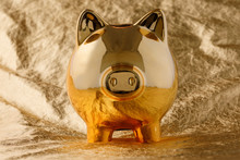 Piggy Bank Golden On A Gold Background. Business And Finance.