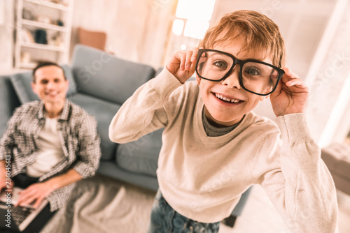 Photo  Little boy amusing himself by wearing his father's reading glasses