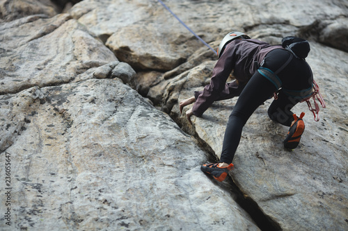 A girl climber climbs the rocky cracks. Competitions in rock climbing.