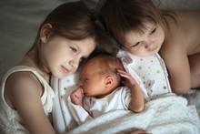 Sisters Care Hug Newborn, Baby Sleeping In Cocoon
