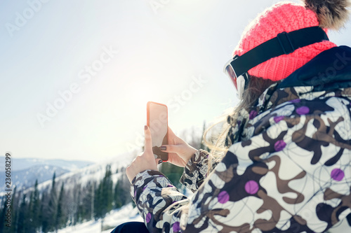 Fotografía  Woman snowboarder relaxing after snowboarding, taking photos of winter nature in