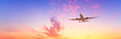 canvas print picture - Airplane flying above dramatic clouds during sunset