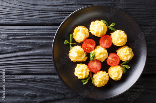 Appetizing snack Duchess Potatoes closeup on a black plate on a table. horizontal top view