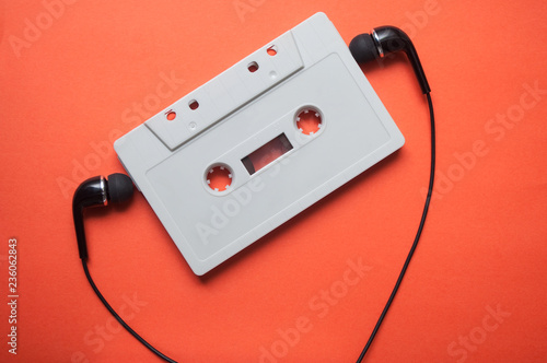 Photo closeup of vintage audio cassette with black earphones on orange background