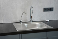 Modern Kitchen With Faucet And Metal Kitchen Sink And Outlets.