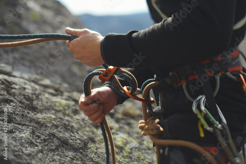 Photo Easy belay-descender device in the hands of a climber closeup