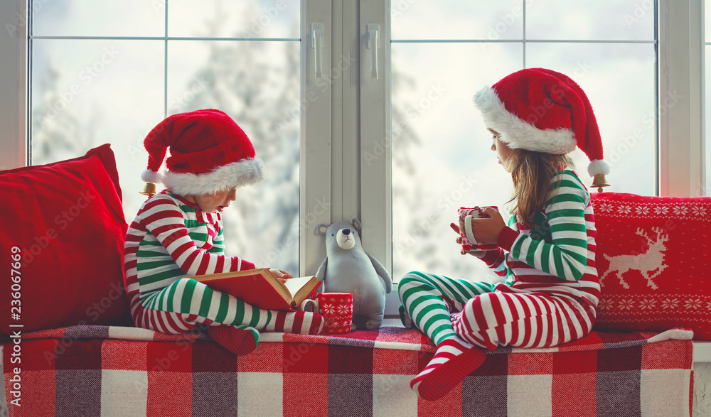 Fototapety, obrazy: children girl and boy is sad on Christmas morning by the window.