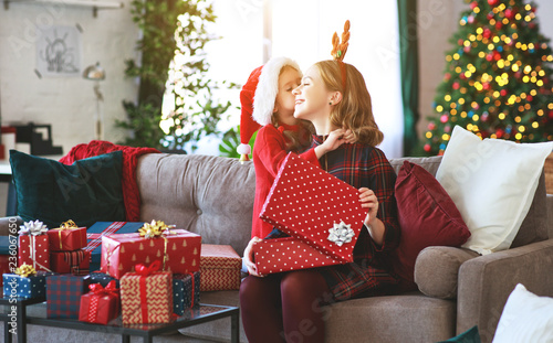 family mother and child daughter open presents on Christmas morning