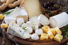 Cheese Platter With A Variety Of Types Of Cheese - Gorgonzola, Mozzarella, , Camembert, Toma, Emmental And Fresh Caprino - Served On Rustic Wood With Olives And Breadsticks