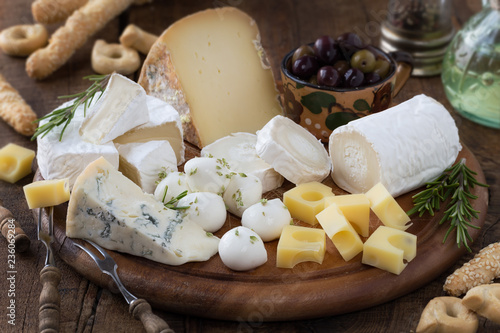 Fototapeta Cheese platter with a variety of types of cheese - gorgonzola, mozzarella, , camembert, toma, emmental and fresh caprino - served on rustic wood with olives and breadsticks obraz