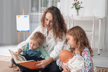 Young Mother Or Nanny With Small Children, A Boy And A Girl, Sit On The Floor On A Rug In The Room At Home And Read A Book, Play With  A Doll