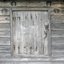 Old Small Worn And Weathered Wooden Door On Log Wall. Horshoes Above.