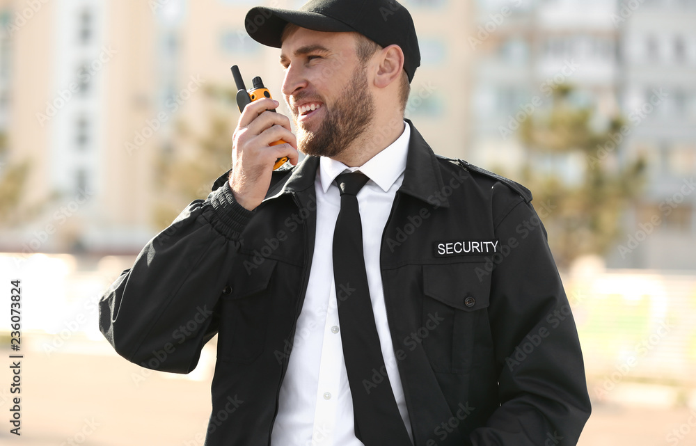 Fototapeta Male security guard with portable radio transmitter outdoors