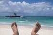 feet of a man lying on the sand of a beach paradise symbol of happiness and holidays
