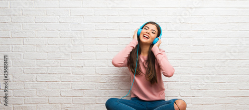Photo  Teenager girl sitting on the floor in a room listening to music with headphones