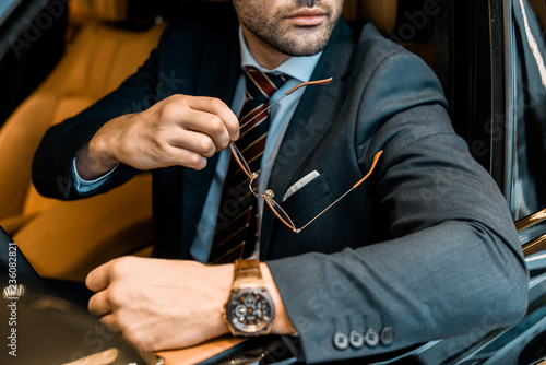 partial view of businessman with luxury watch holding eyeglasses while sitting in car