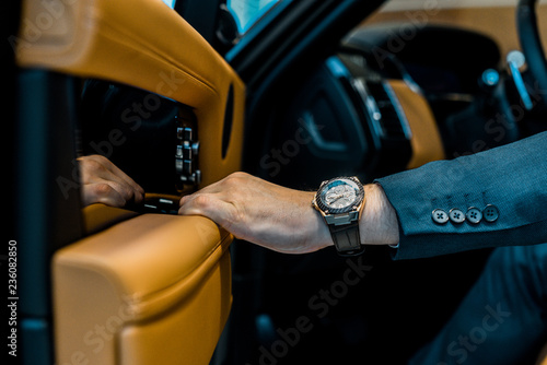 Fotografía cropped image of businessman with luxury watch closing door while sitting in car