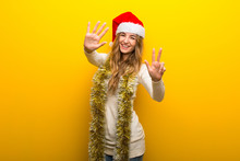 Girl Celebrating The Christmas Holidays On Yellow Background Counting Eight With Fingers