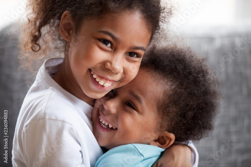 Valokuva  Happy African American siblings embracing, sitting together on couch at home in