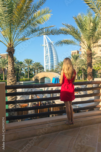 Fotomural Young tourist woman dressed in red dress looking Burj al Arab from Madinat Jumeirah souk with shopping bags next to her