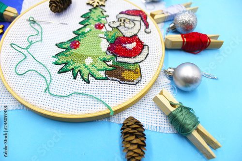 Picture embroidered with a cross child, preparing for the New Year and  Christmas. Christmas tree green, Santaklaus of thread. Accessories and  tools for embroidery. Festive mood, holiday. - Buy this stock photo