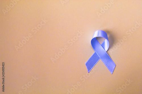 Fototapeta Blue ribbon prostate cancer symbol on pastel background. Awareness and healthcare concept.  Copy space. obraz na płótnie