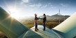 Happy engineer and businessman shake hands after good work. They standing a top of windmill. Around wind generators and beautiful sunset landscape