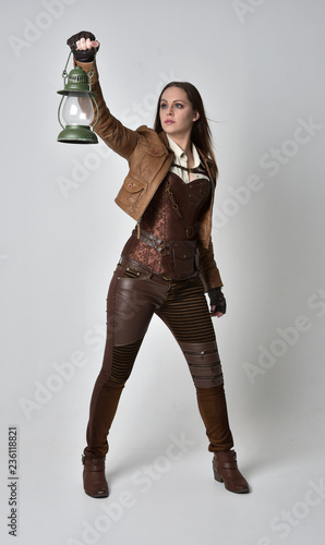 Fotografiet full length portrait of brunette  girl wearing brown leather steampunk outfit