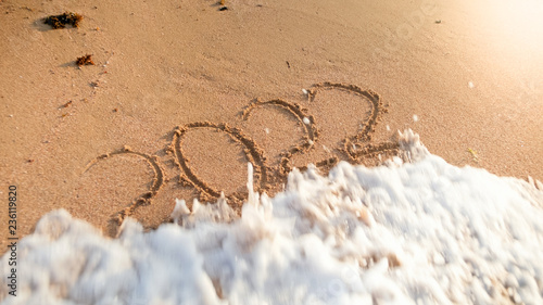 Fotografia  Closeup photo of ocean wave rolling over 2022 New Year numbers written on wet sand at island beach
