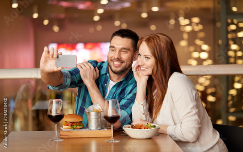 leisure, technology and people concept - happy couple having lunch and taking selfie by smartphone at restaurant