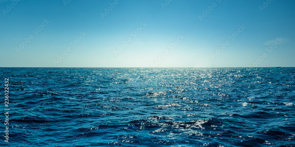 Fototapeta Blue ocean panorama with sun reflection, The vast open sea with clear sky, Ripple wave and calm sea with beautiful sunlight