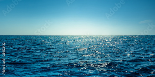 Foto Blue ocean panorama with sun reflection, The vast open sea with clear sky, Rippl