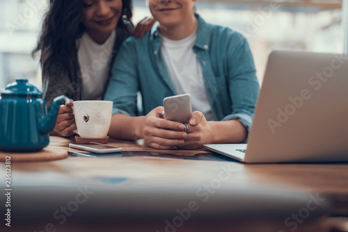 Relaxed young woman smiling and putting one hand on the shoulder of her boyfriend and looking at his smartphone