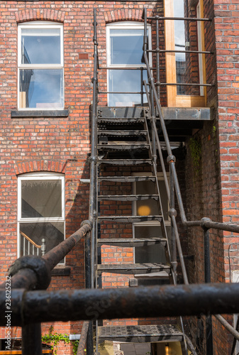 urban new york  style metal vintage steel fire escape ladder stairs in manchester england Fototapeta