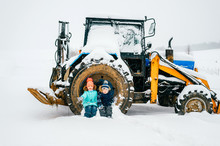 Children Sit In Tractor Wheel On Winter Day Outdoors