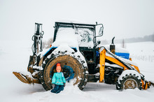 Girl Sitting In A Tractor Wheel On A Winter Day Outdoors