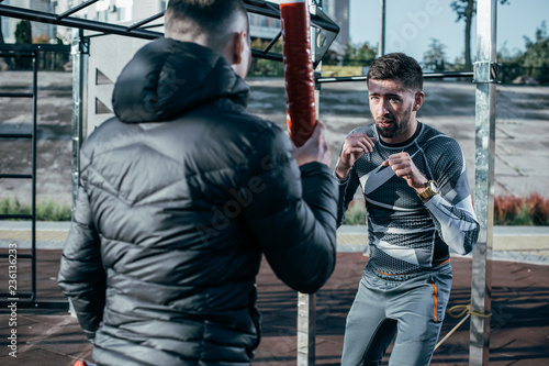 Fotografia  Reliable trainer holding boxing sticks while the boxer mastering punches