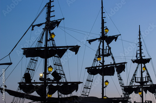 romantic atmosphere shot of old vintage ship mast and sails black shapes silhouettes with small lamps yellow illumination in evening blue sky background