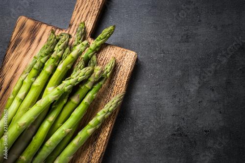 Fresh green asparagus on black slate background. Wallpaper Mural