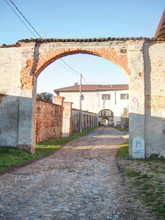 The Stone Made Entrance Arch Of The Small Rural Badia Di Dulzago Hamlet, With Stone Paved Road, In Bellinzago, Piedmon Region, Italy