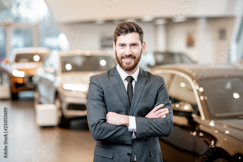Photographie Portrait of a handsome salesman in the suit standing at the showroom with luxury