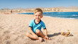 Portrait of cute three years old toddler boy sitting on the sandy beach at sea.