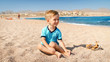 Portrait of happy laughing toddler boy sitting at the sea beach at bright sunny day.