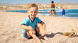 Portrait of adorable toddler boy enjoying sitting on the beach at sea