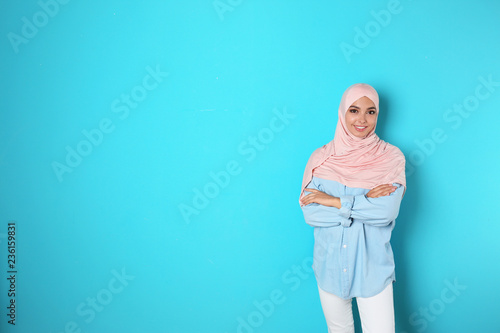 Portrait of young Muslim woman in hijab against color background. Space for text