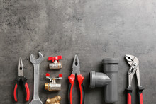 Flat Lay Composition With Plumber's Tools And Space For Text On Gray Background